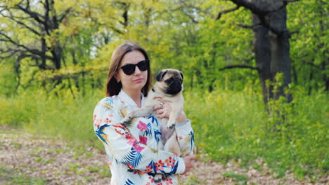 Young-Stylish-Woman-In-Sunglasses-Walking-In-The-Park-With-A-Dog-Of-Pug-Breed-2