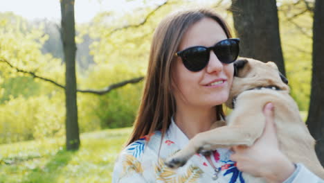 Young-Stylish-Woman-In-Sunglasses-Walking-In-The-Park-With-A-Dog-Of-Pug-Breed-3