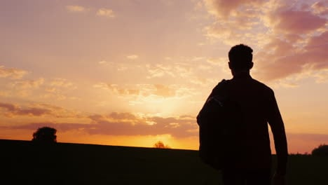 A-Teenager-With-A-Backpack-Looks-Forward-To-The-Sun-And-The-Horizon