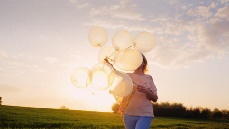 Carefree-Young-Woman-With-Balloons-Walking-On-A-Green-Meadow-At-Sunset-1