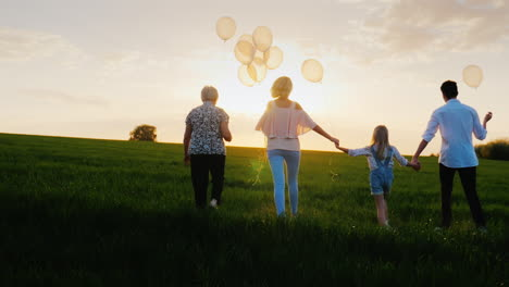 A-Large-Family-With-Children-Is-Walking-Along-The-Green-Meadow-Towards-The-Sunset