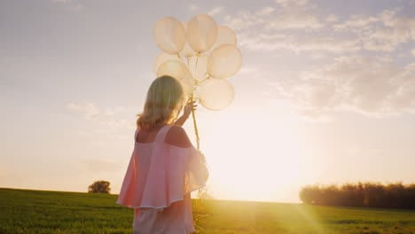 Carefree-Young-Woman-With-Balloons-Walking-On-A-Green-Meadow-At-Sunset-3