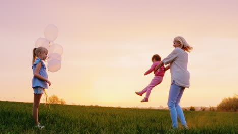 A-Happy-Mother-Of-Two-Girls-Playing-With-Them-At-Sunset