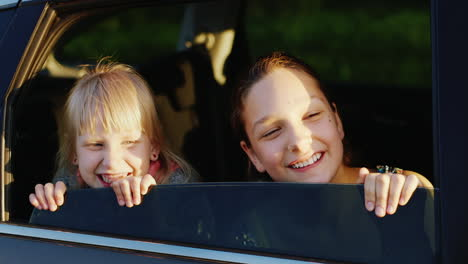 Two-Fun-Girls-6-And-11-Years-Old-Are-Looking-Out-The-Car-Window