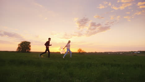 A-Man-And-A-Woman-Have-Fun---Running-Around-The-Field-At-Sunset-With-Balloons