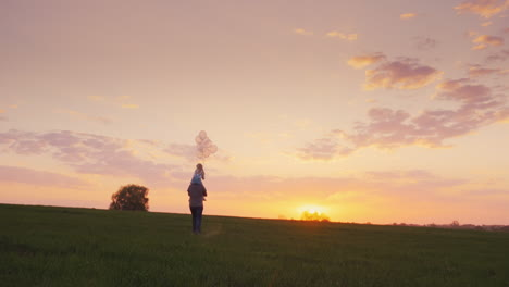 Father-Carries-His-Daughter-With-Balls-Across-The-Field-At-Sunset