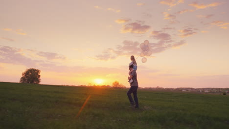 Father-Carries-His-Daughter-With-Balls-Across-The-Field-At-Sunset-1