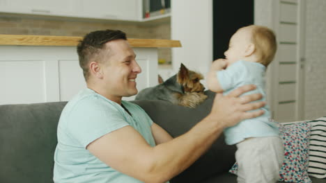 A-Happy-Father-Plays-With-His-Young-Son-At-Home