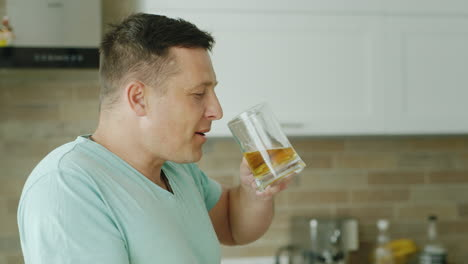 A-Young-Caucasian-Man-Drinks-Beer-In-His-Kitchen