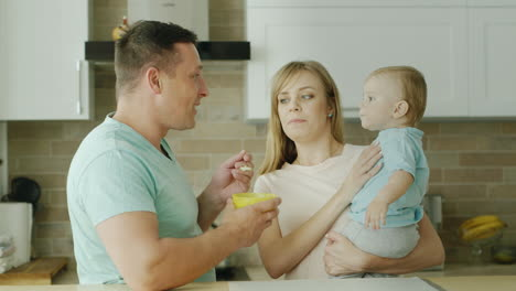 Young-Parents-Play-With-Their-Little-Son-While-They-Try-To-Feed-Him-From-A-Spoon