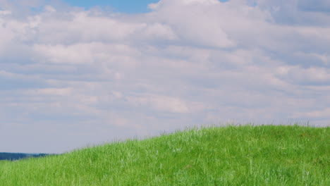 Green-Hill-Against-The-Blue-Sky-With-Clouds