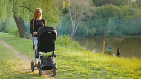 Young-Caucasian-Mother-Walking-In-The-Park-With-A-Stroller