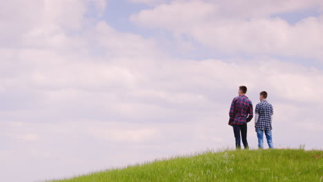 Two-Young-Men-Stand-On-Top-Of-A-Green-Mountain