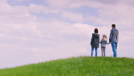 A-Family-Of-Three-People---Father-Mother-And-Daughter-6-Years-Old-Stand-On-Top-Of-A-Green-Hill