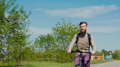 A-Young-Bearded-Man-Is-Riding-A-Bicycle