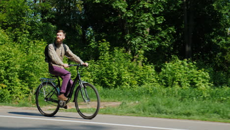 Bearded-Hipster-Riding-On-A-Bike-On-A-Clear-Spring-Day