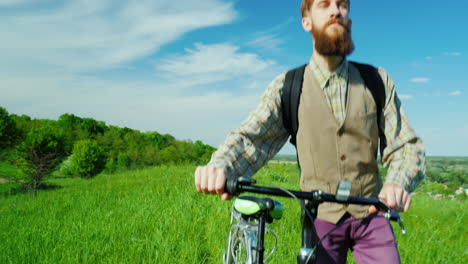 A-Young-Hipster-Man-Walks-With-A-Bicycle-Over-A-Green-Meadow