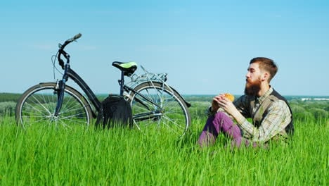 Young-Man-Eating-A-Hamburger-While-Sitting-On-A-Green-Meadow-Near-His-Bicycle