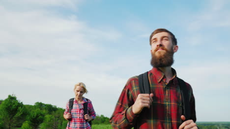 A-Couple-Of-Tourists-With-Backpacks-Are-Walking-Along-The-Crest-Of-A-Large-Green-Hill-3