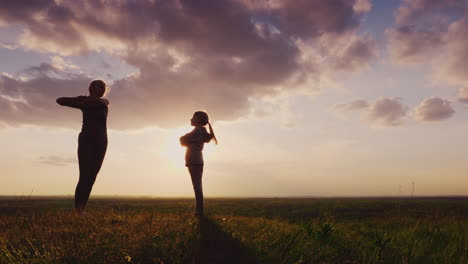 Silhouette-Of-A-Young-Woman-With-A-Child-Doing-Fitness-In-Nature-2