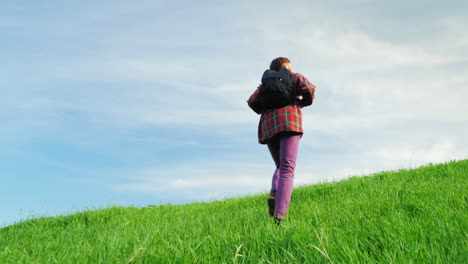 A-Young-Man-With-A-Backpack-Behind-Him-Rises-To-The-Top-Of-A-Large-Green-Hill