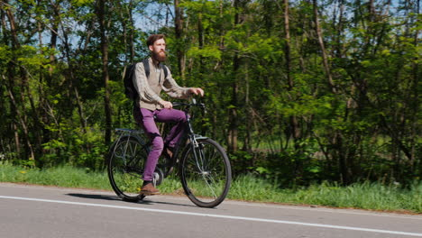 An-Attractive-Man-With-A-Beard-Rides-A-Bike-Along-A-Bicycle-Path