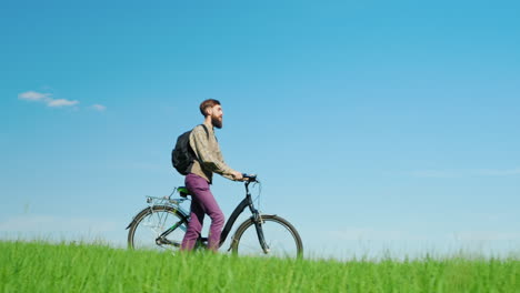A-Young-Hipster-Man-Drives-A-Bicycle-Through-A-Green-Meadow