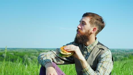 A-Young-Bearded-Man-Eating-A-Hamburger-Outdoors