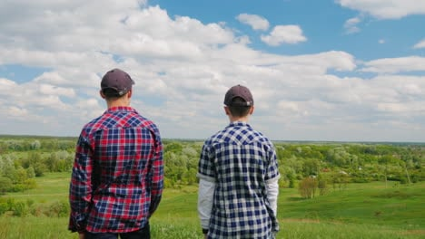 Two-Young-Men-Stand-On-Top-Of-A-Green-Mountain-1