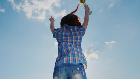 A-Young-Woman-With-A-Champion-s-Cup-Jumps-High-Up-Towards-The-Sky