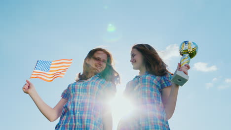 Two-Teenage-Twins-Girls-With-A-Winner-s-Cup-And-An-American-Flag