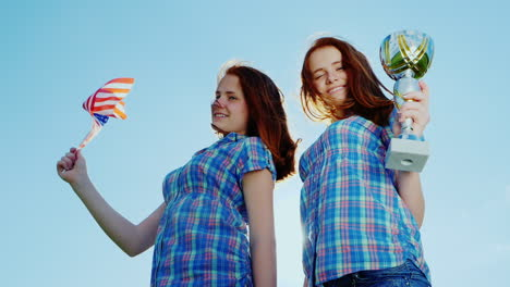 Two-Teenage-Twins-Girls-With-A-Winner-s-Cup-And-An-American-Flag-1