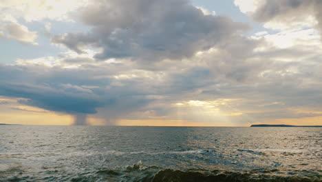A-Rain-Cloud-With-Rain-Over-The-Sea-And-A-Setting-Sun-With-Beautiful-Rays