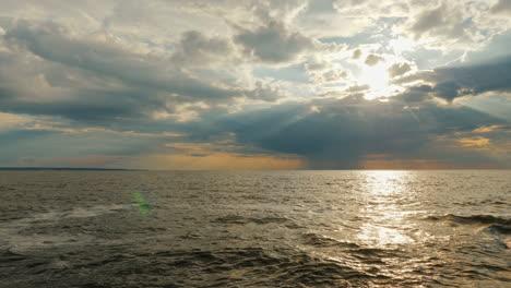 A-Rain-Cloud-With-Rain-Over-The-Sea-And-A-Setting-Sun-With-Beautiful-Rays-1