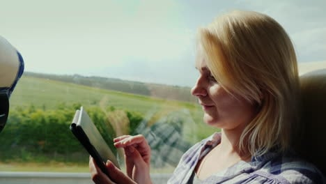 Side-View-Of-A-Young-Woman-Traveling-By-Bus-And-Using-A-Tablet
