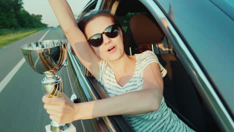 A-Young-Woman-With-A-Winner-s-Cup-In-Her-Hand-Looks-Out-The-Window-Of-A-Moving-Car-Emotionally-Rejoicing