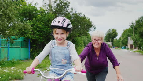 Grandmother-Teaches-Her-Granddaughter-How-To-Ride-A-Bicycle
