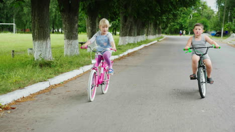 Two-Carefree-Children---A-Girl-And-A-Boy-Ride-Bicycles-On-The-Street