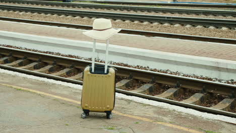 Travel-Bag-With-A-Hat-On-A-Background-Of-A-Railroad