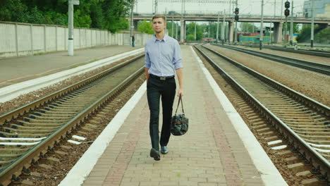 A-Good-Looking-Young-Businessman-Walks-Along-The-Railway-Platform-1
