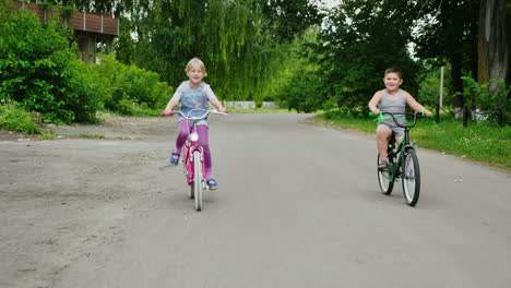 Two-Farm-Children-Are-Riding-Bicycles-In-The-Countryside