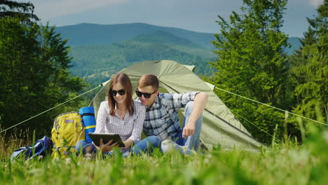 A-Young-Couple-Is-Using-A-Laptop-While-Camping-With-A-Tent