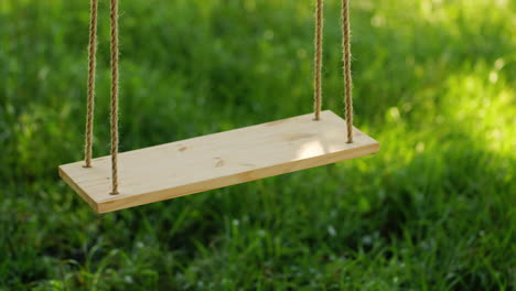 Wooden-Swing-On-A-Background-Of-Green-Grass