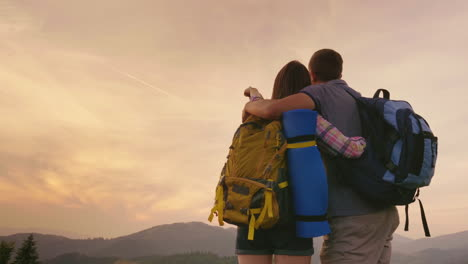 A-Young-Couple-Of-Tourists-With-Backpacks-Look-Up-At-The-Airplane-In-The-Sky