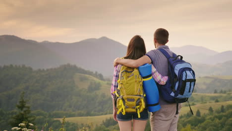 A-Young-Couple-Of-Tourists-With-Backpacks-Look-Up-At-The-Airplane-In-The-Sky-1
