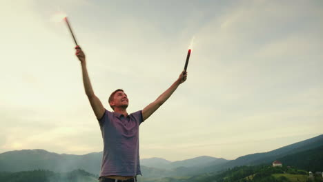 A-Man-In-The-Mountains-Signals-With-Hand-Fireworks-Looks-Up