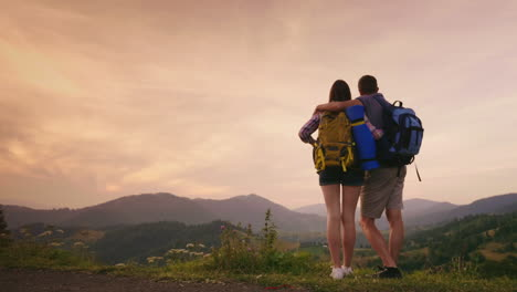 A-Young-Couple-Of-Tourists-With-Backpacks-Look-Up-At-The-Airplane-In-The-Sky-2