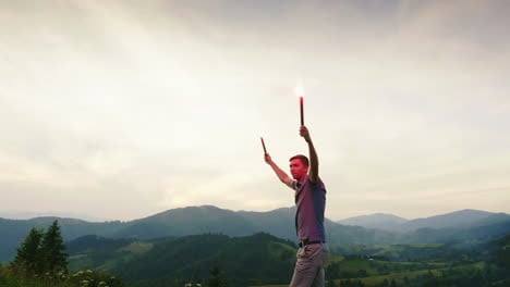 A-Man-In-The-Mountains-Signals-With-Hand-Fireworks-Looks-Up-1
