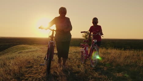 An-Elderly-Lady-Walks-With-Her-Granddaughter-Bicycles-At-Sunset
