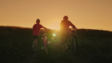 An-Elderly-Lady-Walks-With-Her-Granddaughter-Bicycles-At-Sunset-1